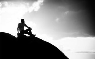 man on rock thinking