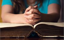 Young Woman Praying With Bible