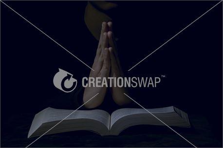 Hands praying on bible (45056)