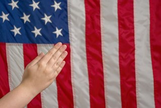 Praying hands in front of Flag