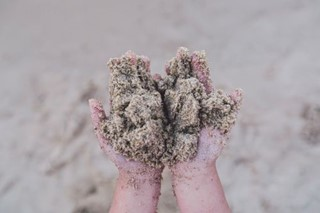 Child holds sand in the hands