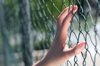 Female Hand on Fence