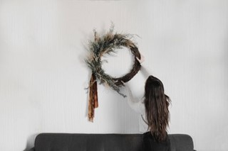Girl placing Christmas Wreath