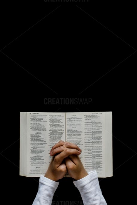 Praying hands over a bible (66275)