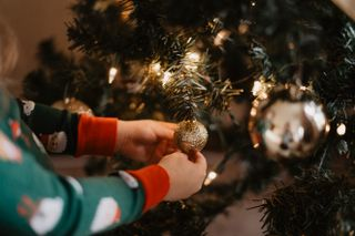 Child placing ornament on tree