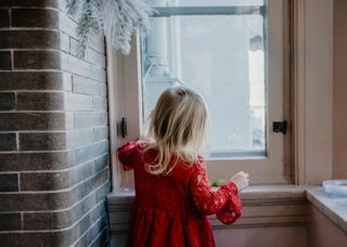 Little girl playing at window