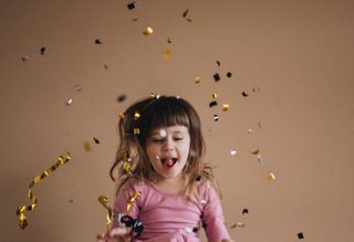 little girl throwing confetti