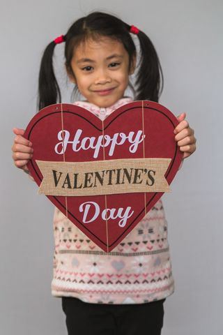 child holding a valentine sign