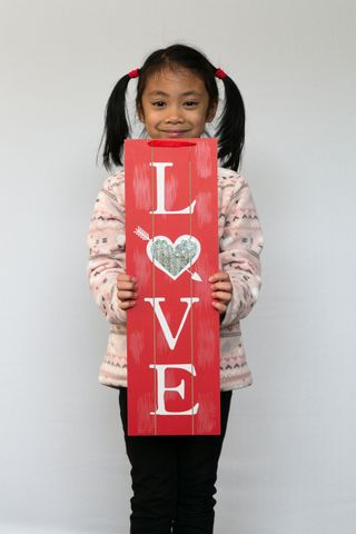 A child holding a love sign