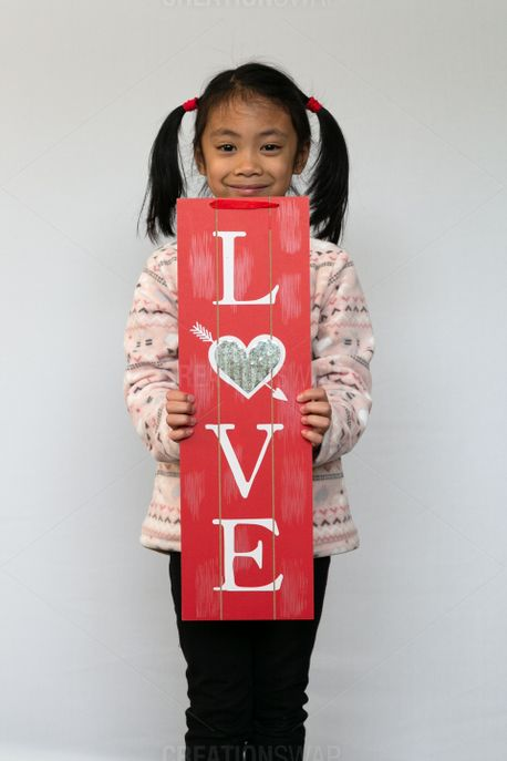 A child holding a love sign (76085)