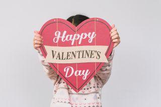 child holding a valentine sign