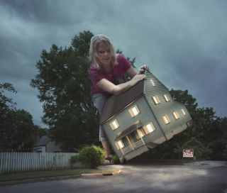 Woman lifts a large house